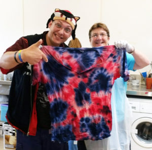 Photo of 2 people holding tie dye shirt
