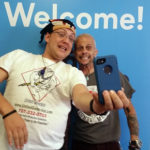 """Photo of participants in front of """"welcome"""" sign"""
