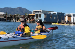 Photo of kayakers by houseboats