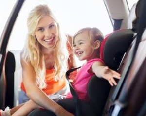 image of mom putting child in car seat